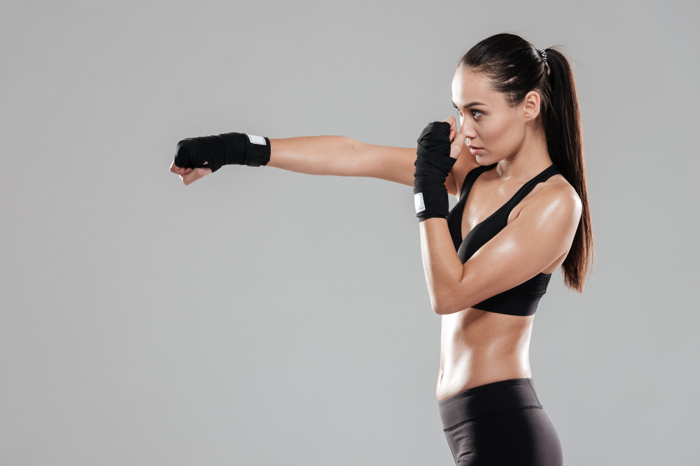 Photo of pretty young boxer woman practicing over grey background. Look aside.