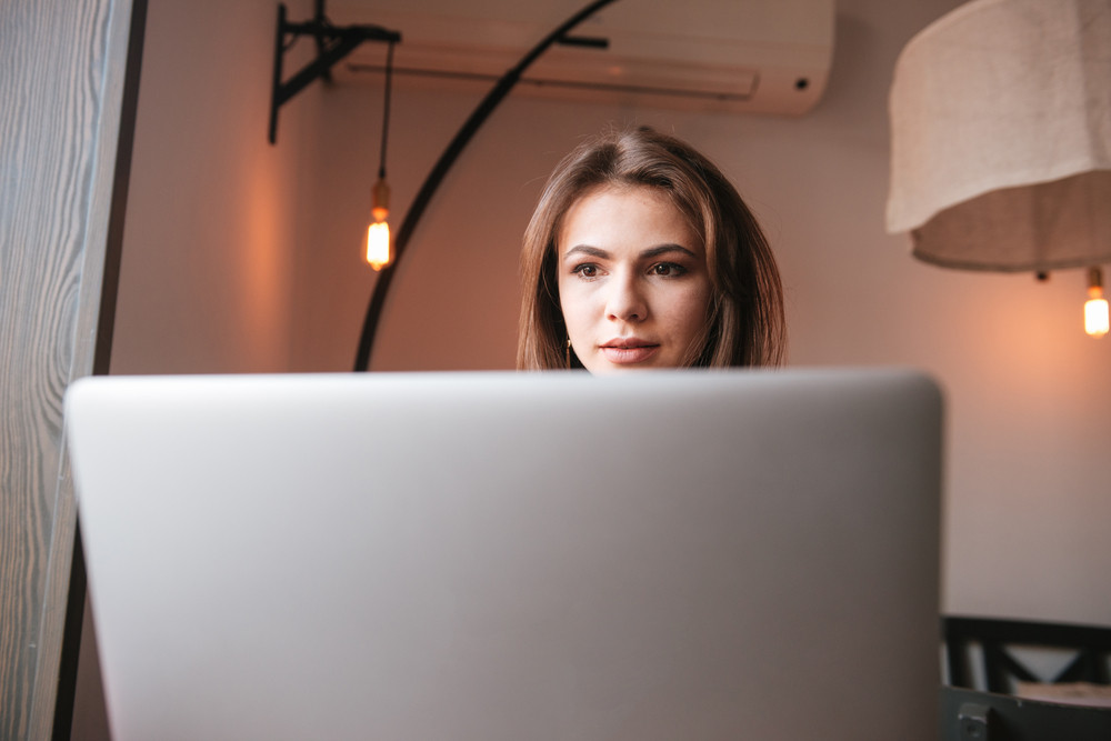 Photo of pretty young woman sitting at the table in cafe and using laptop computer. Look at laptop.