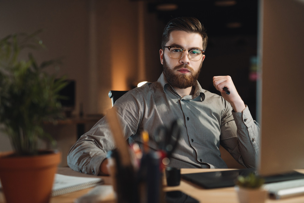 Photo of serious bearded web designer dressed in shirt working late at night and looking at camera while holding pen in hand.