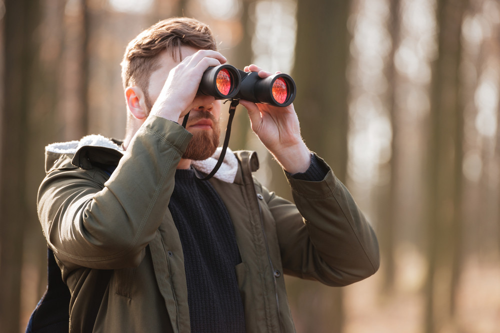 Photo of serious bearded young man looking at field-glass standing in the forest.