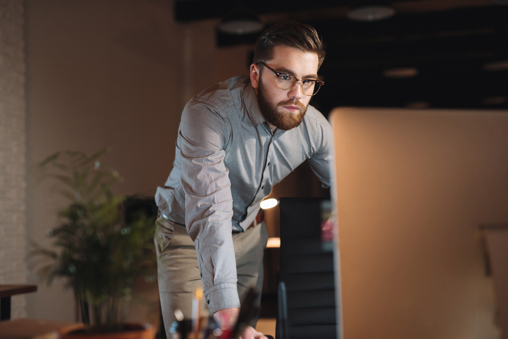 Photo of serious web designer dressed in shirt and wearing eyeglasses working late at night.