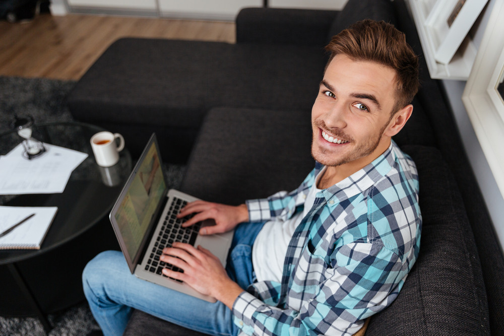 Photo of smiling bristle man dressed in shirt in a cage print sitting on sofa in home and using laptop computer. Looking at the camera.