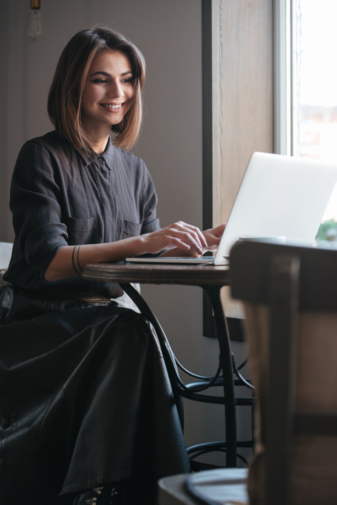 Photo of smiling lady sitting at the table in cafe and using laptop. Look at laptop.
