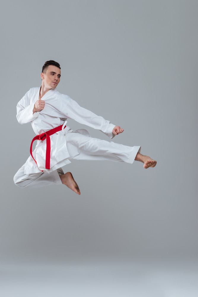 Photo of sportsman in kimono practice in karate while jumping isolated over grey background. Looking aside.