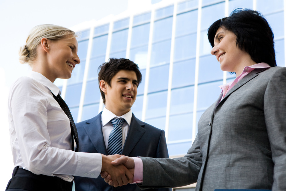 Photo of successful businesswomen handshaking after striking deal while happy man looking at them