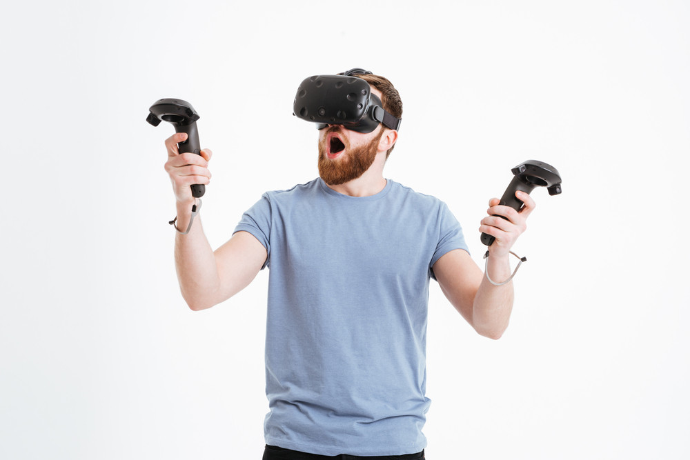 Photo of surprised bearded young man wearing virtual reality device standing over white background while holding joysticks in hands.