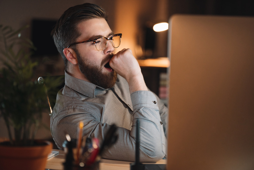 Photo of tired web designer dressed in shirt and wearing eyeglasses working late at night and yawning.