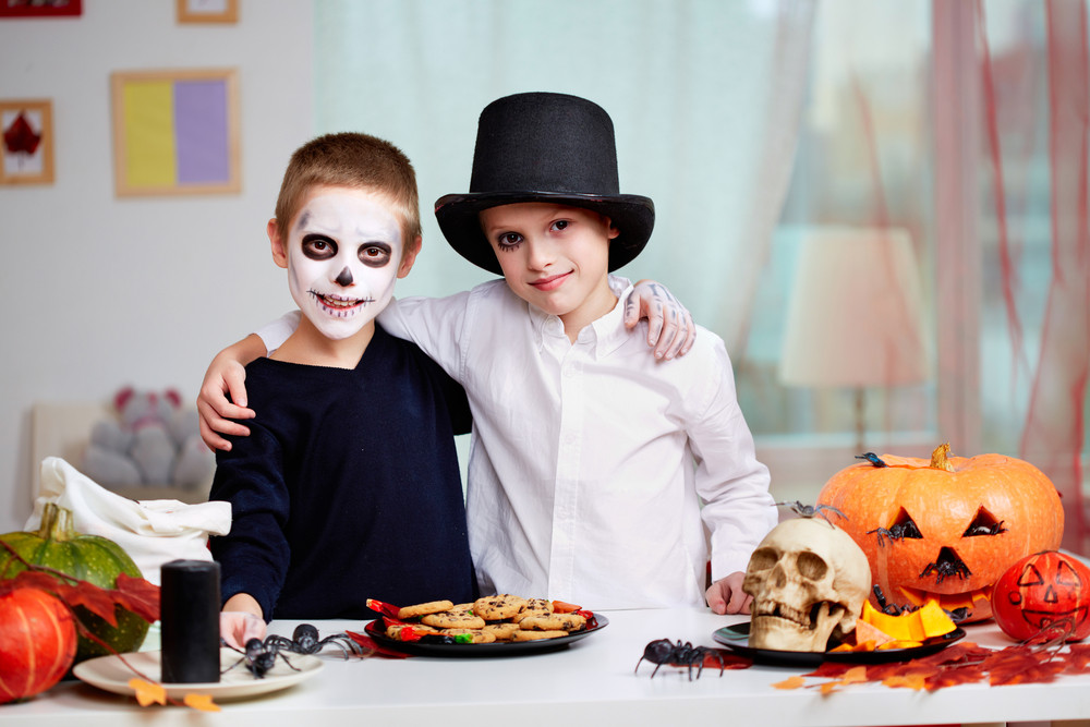 Photo of twin eerie boys looking at camera at Halloween table