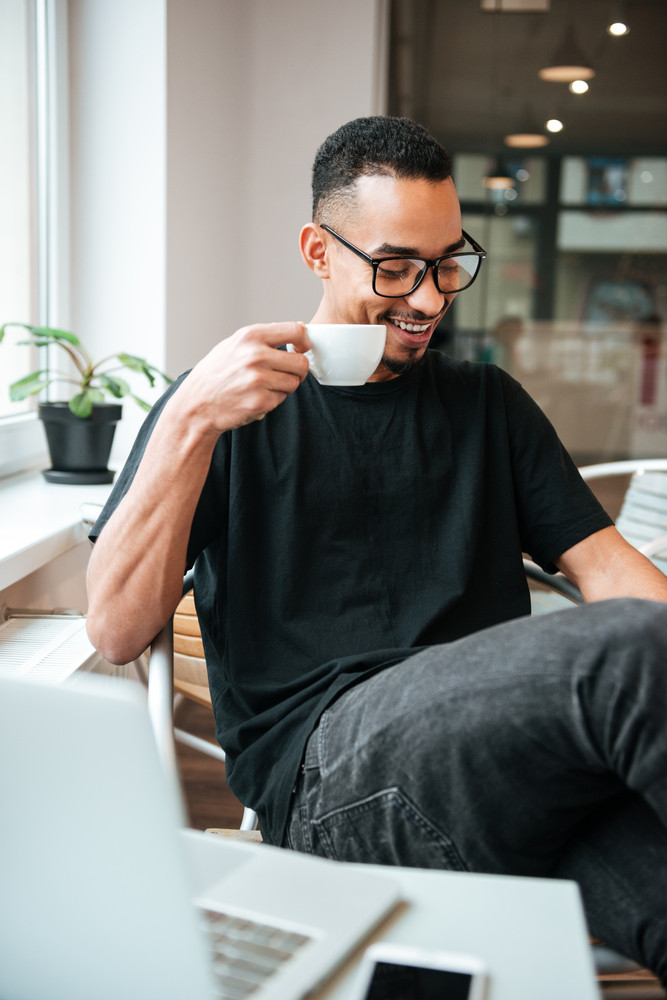 Photo of young african businessman wearing glasses sitting near window and drinking coffee. Coworking.