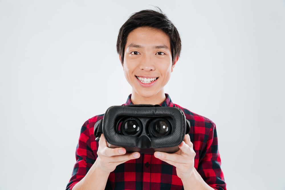 Photo of young asian man dressed in casual shirt in a cage and showing to camera virtual reality device. Isolated over white background.
