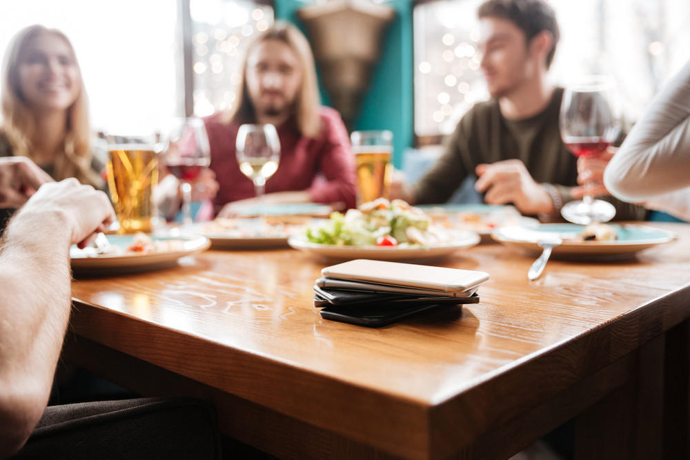 Photo of young attractive friends sitting in cafe eating pizza while drinking alcohol. Focus on lot of mobile phones on table.