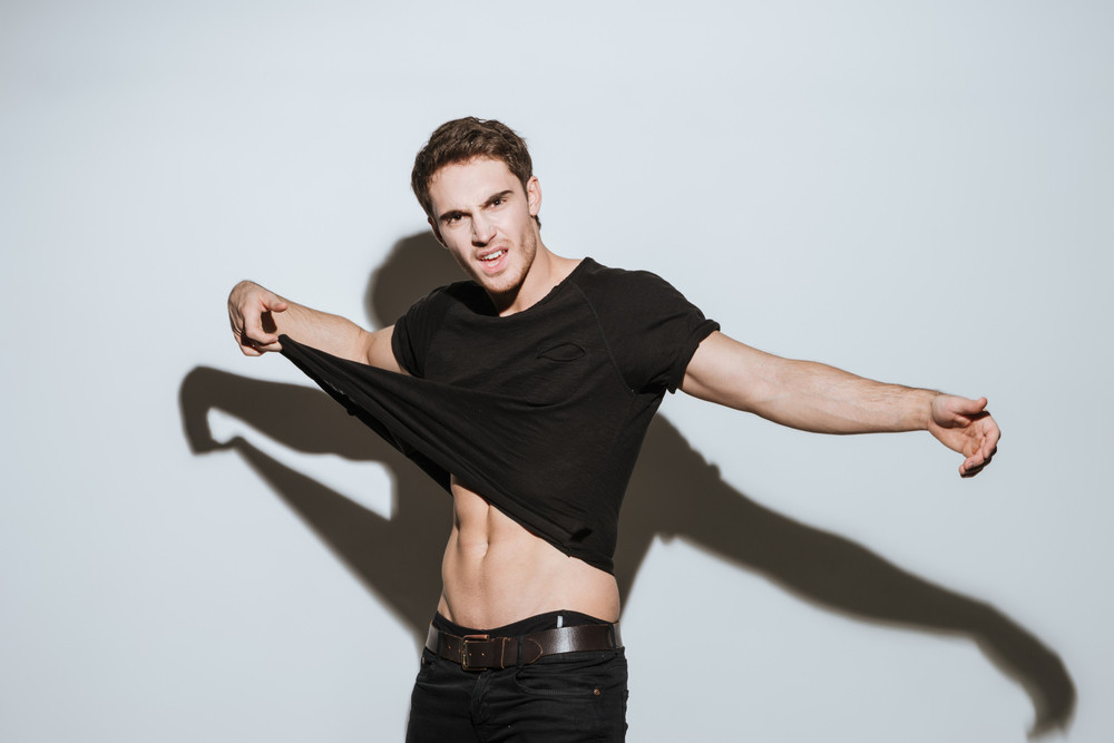 Photo of young attractive man dressed in black t-shirt standing over white background showing his body.