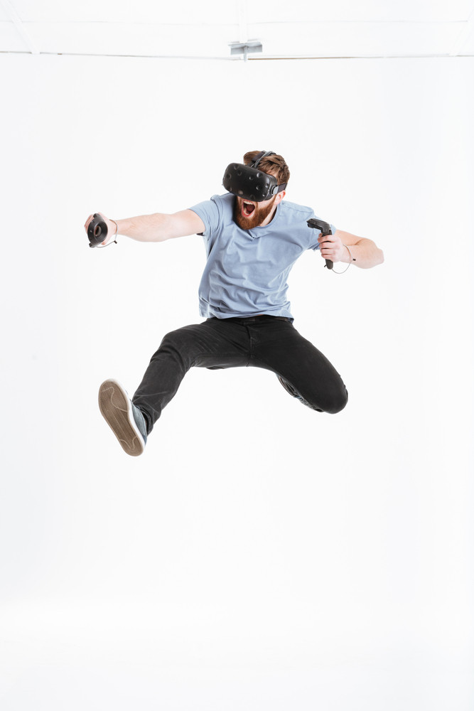 Photo of young bearded screaming man wearing virtual reality device jumping over white background.