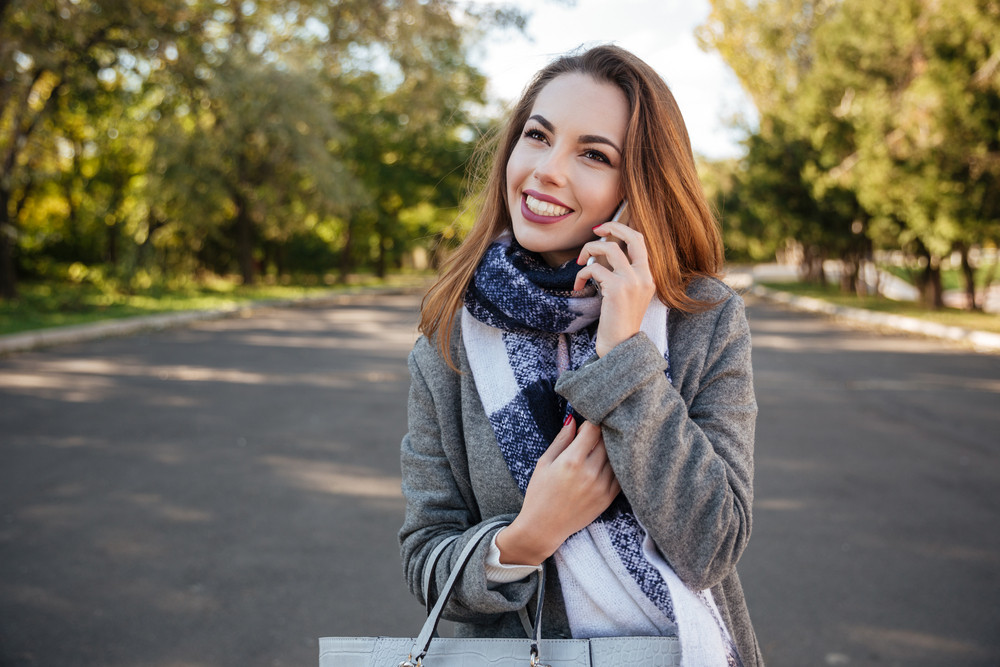 Photo of young beautiful smiling woman talking on cellphone against nature background. Look aside.