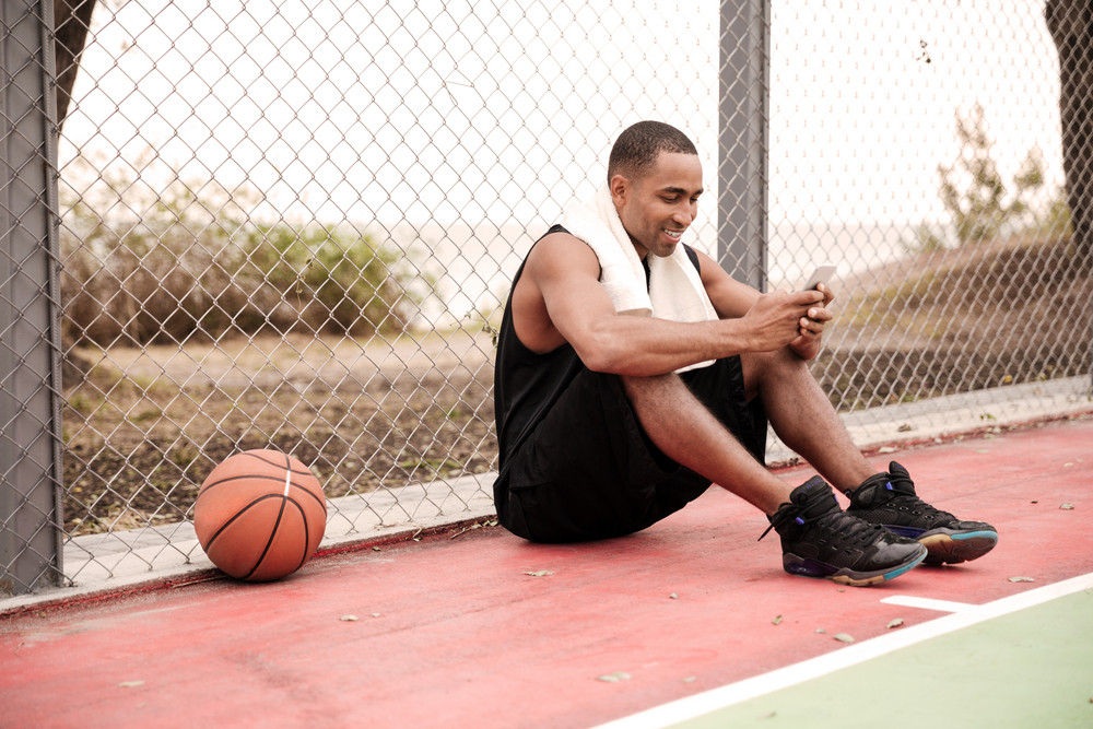 Photo of young cheerful african basketball player sitting in the park with towel near basketball and chatting. Look at phone.
