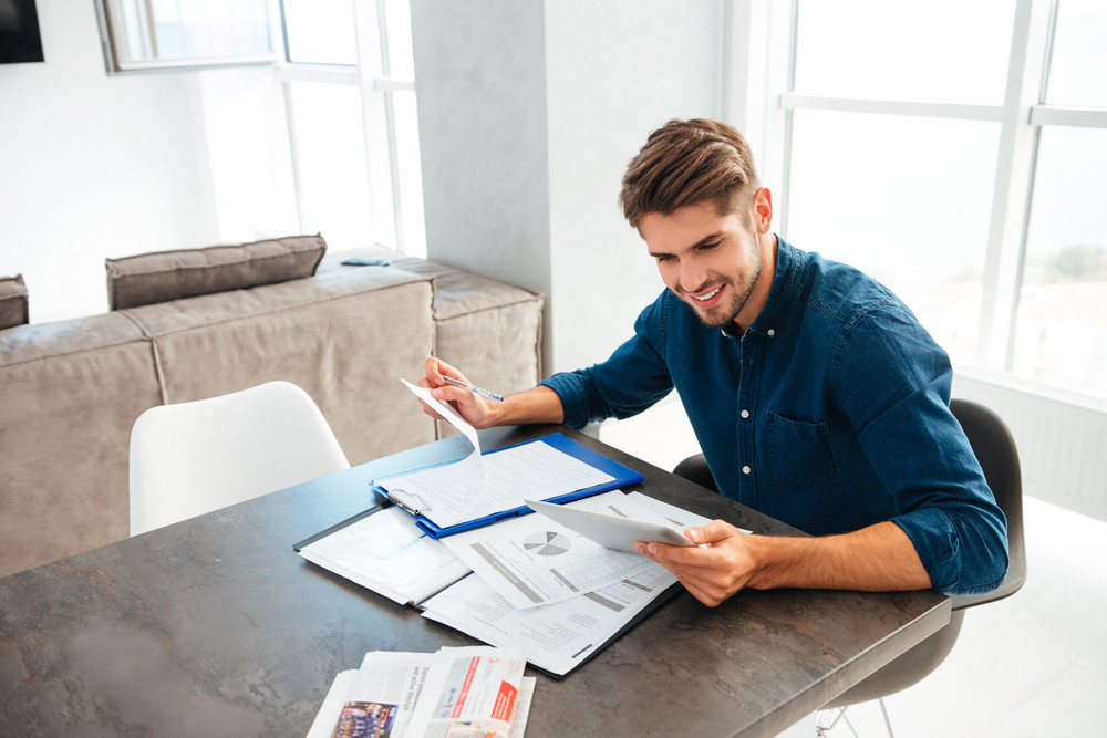 Photo of young cheerful brunette man at home dressed in blue shirt looking at tablet and holding documents in hand.