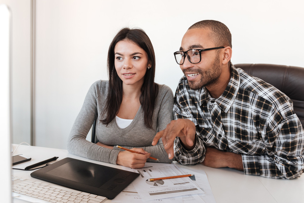 Photo of young cheerful business couple using computer in office. Look at computer.