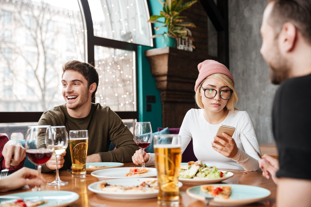 Photo of young cheerful friends sitting in cafe eating and drinking alcohol.