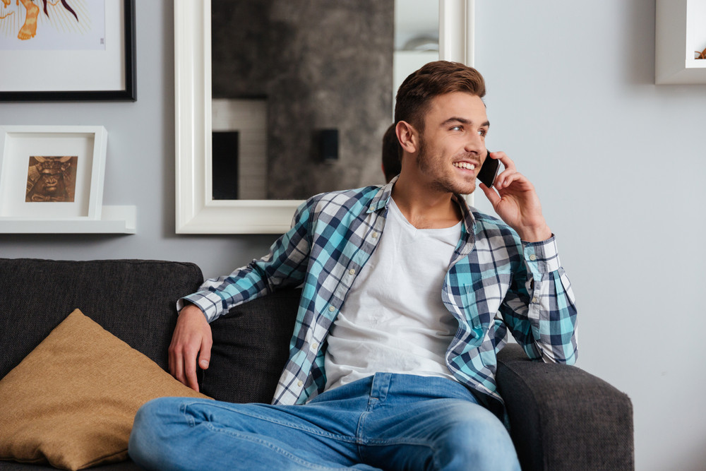 Photo of young cheerful man dressed in shirt in a cage print sitting on sofa in home and talking by his phone. Looking aside.