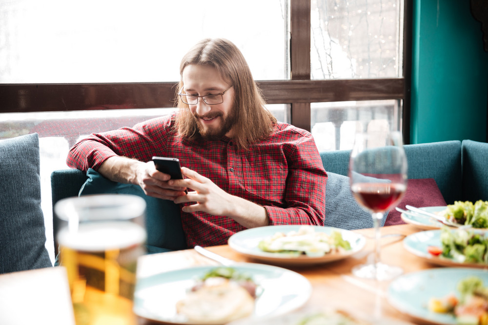 Photo of young cheerful man sitting in cafe while using mobile phone.