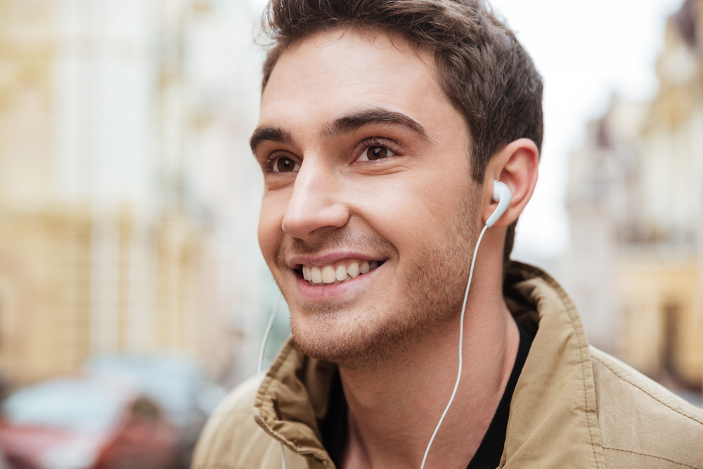 Photo of young cheerful man walking on the street and looking aside while listening music with earphones.