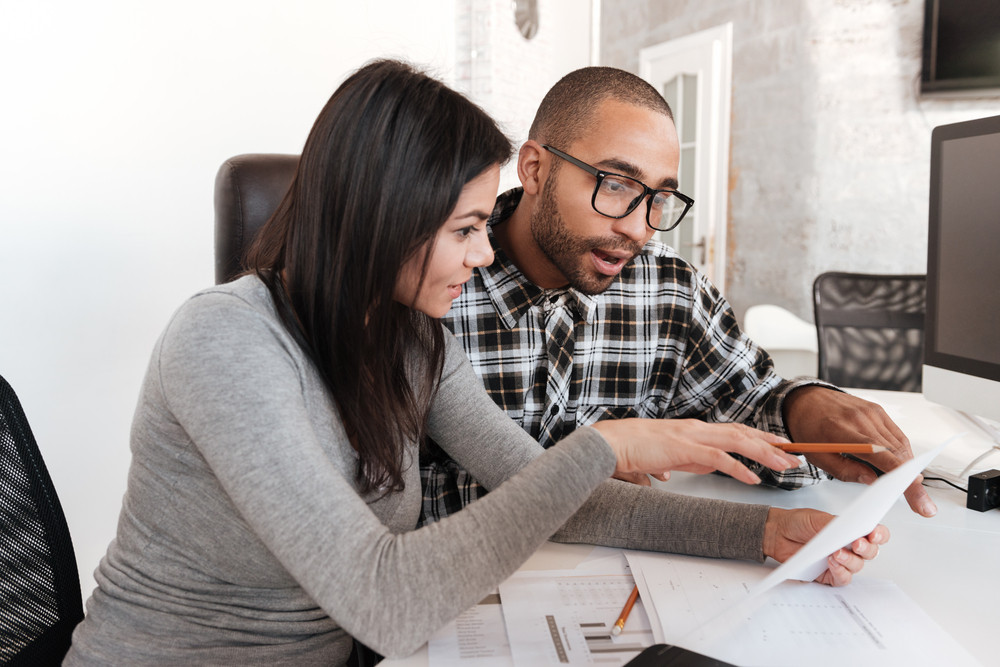 Photo of young concentrated business couple in office holding documents. Look at documents.