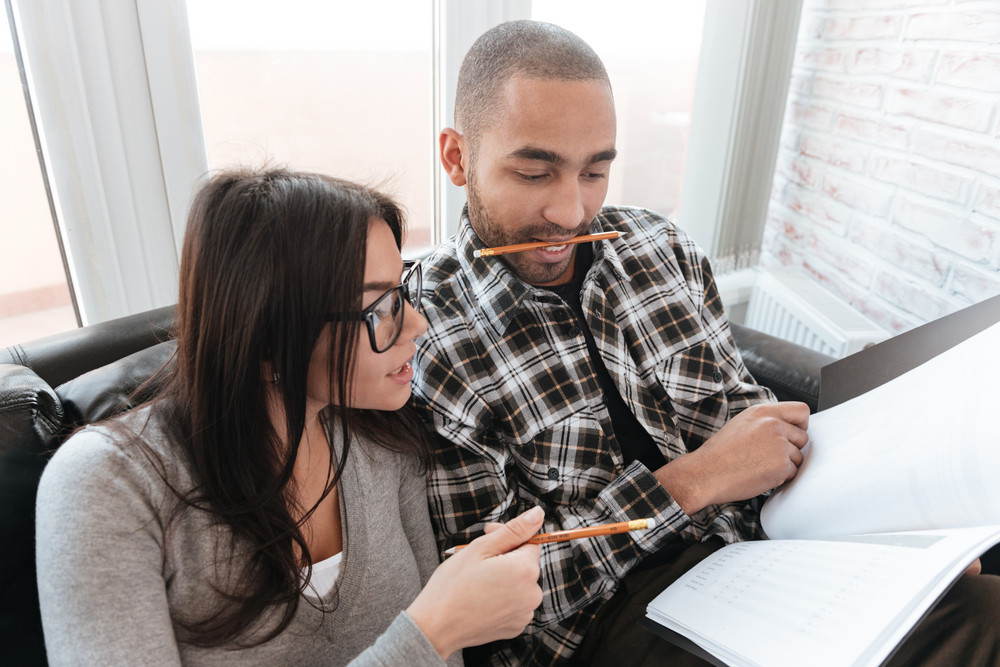 Photo of young concentrated couple sitting on sofa in office holding folder and pencil. Look at folder.