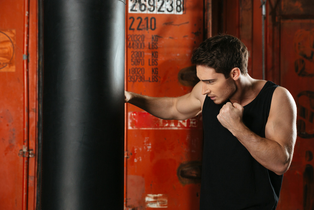 Photo of young concentrated strong boxer training in a gym with punchbag. Looking at punchbag.
