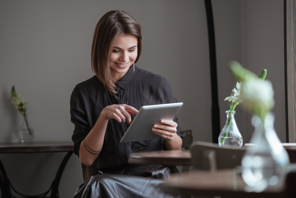 Photo of young cute lady sitting near window in cafe while using tablet computer.