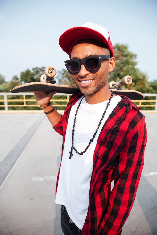 Photo of young dark skinned guy wearing sunglasses and cap holding skateboard. Against the nature background.