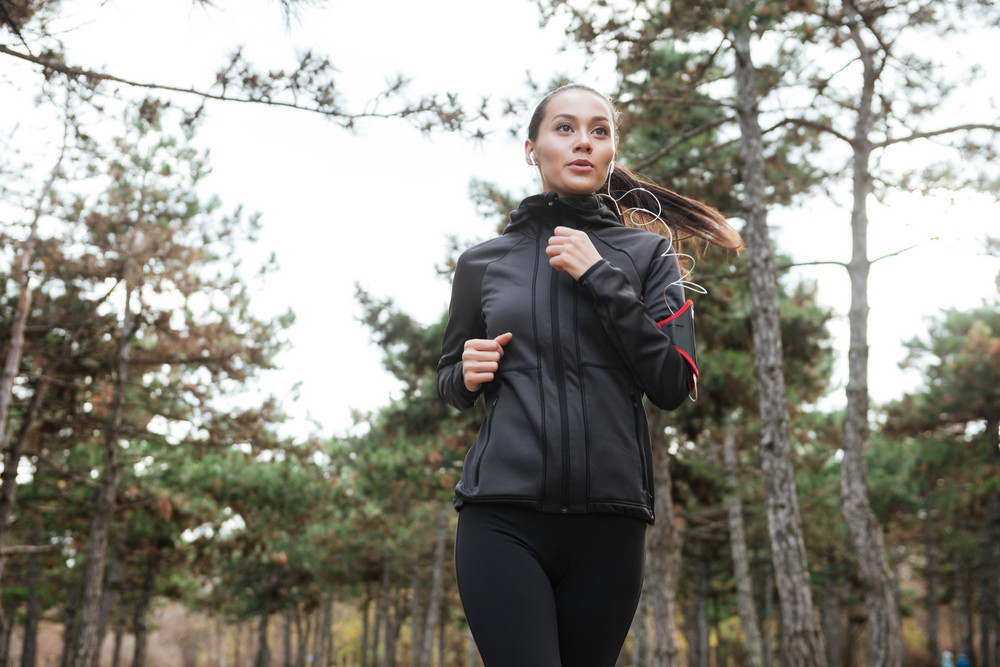Photo of young female runner in warm clothes and earphones running in autumn park