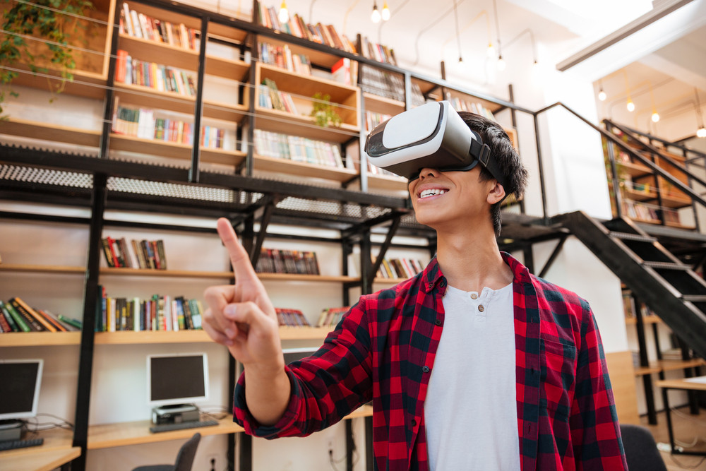 Photo of young happy man dressed in casual shirt in a cage and wearing virtual reality device in the library.