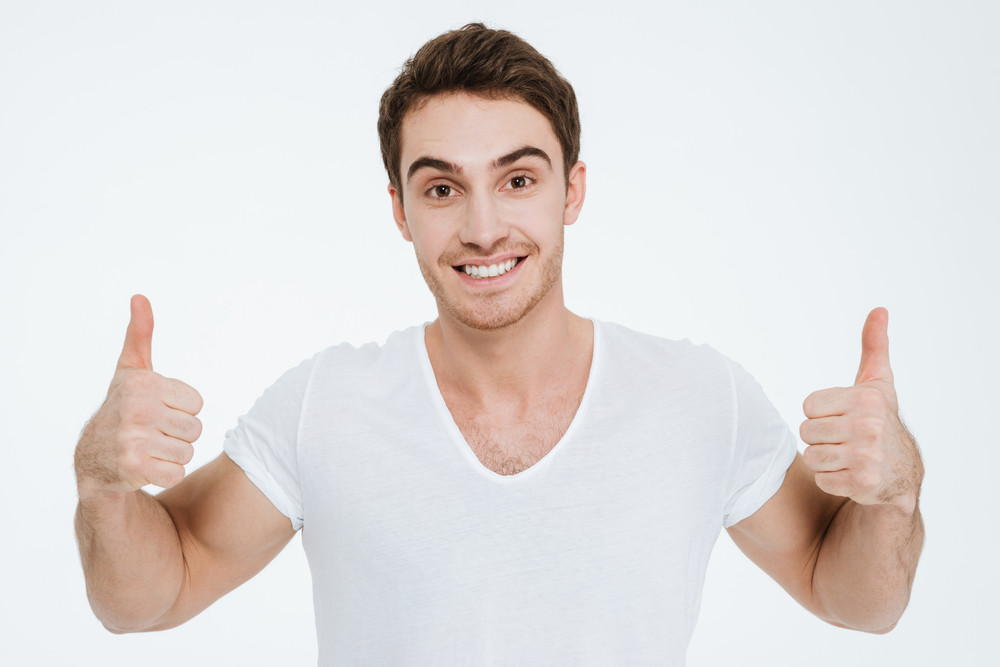 Photo of young happy man dressed in white t-shirt standing over white background make thumbs up gesture.