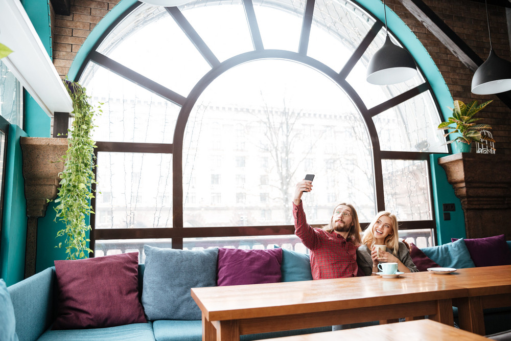 Photo of young loving couple sitting in cafe and talking while drinking coffee and make a selfie.
