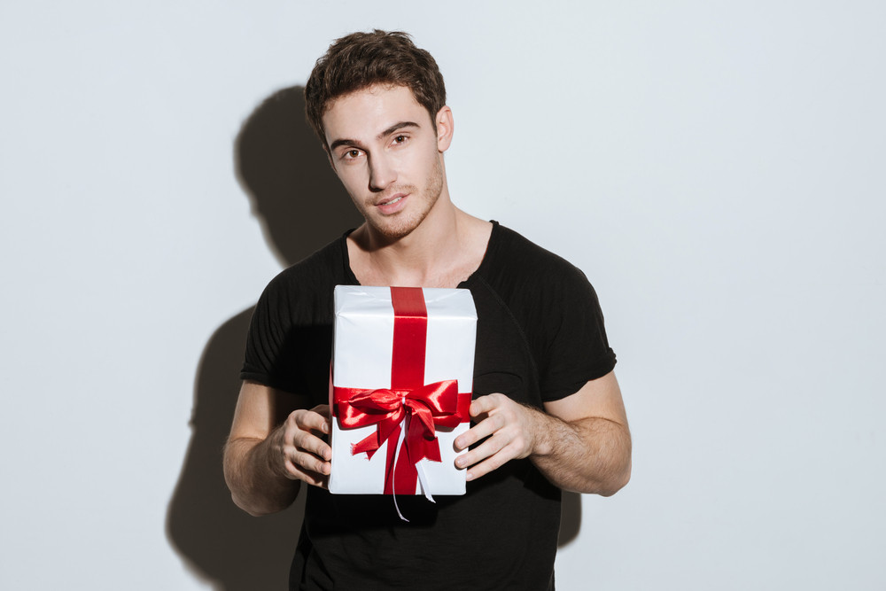Photo of young man dressed in black t-shirt standing over white background holding gift.