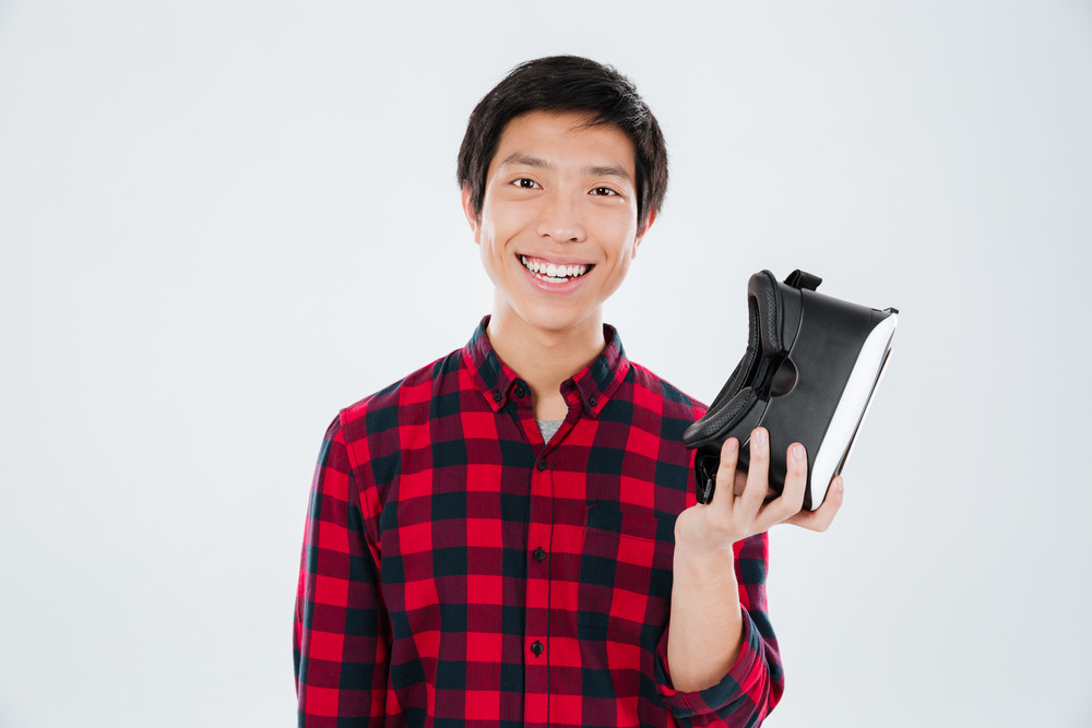Photo of young man dressed in casual shirt in a cage and holding virtual reality device. Isolated over white background.