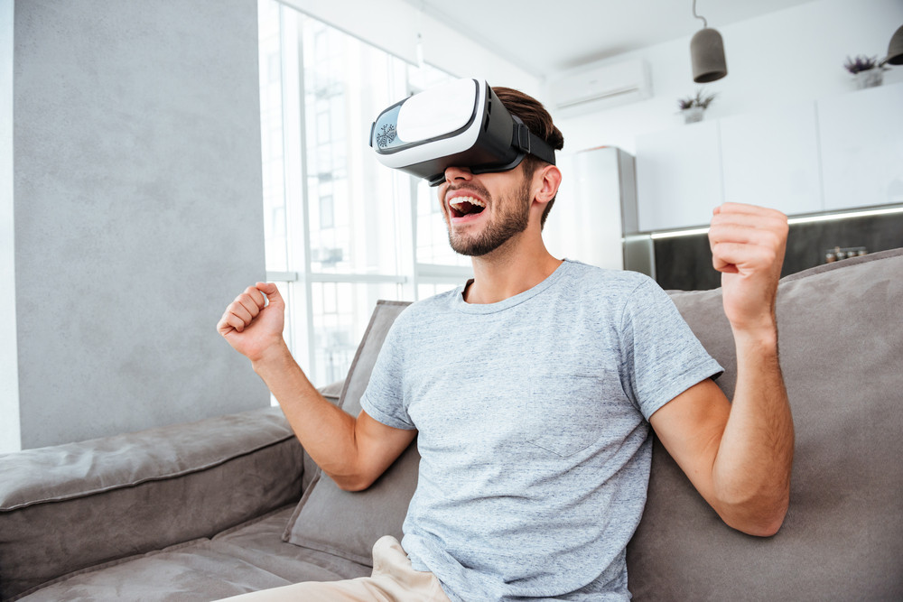 Photo of young man making winner gesture while wearing virtual reality device and sitting on sofa.