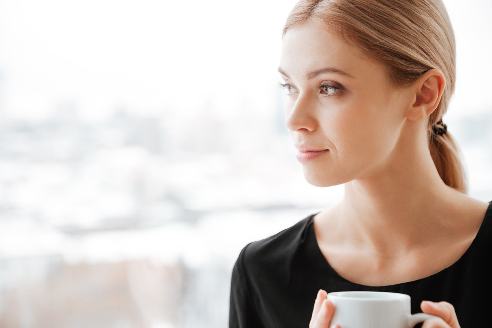 Photo of young pretty woman worker sitting in office near window while drinking hot tea. Looking at window.