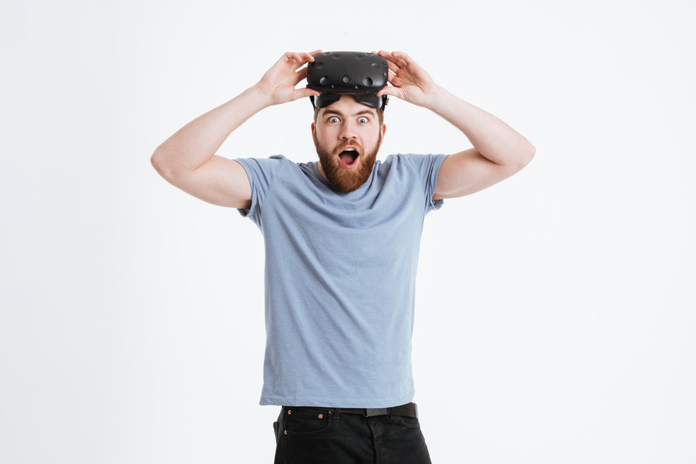 Photo of young shocked bearded man wearing virtual reality device standing over white background and looking at camera.