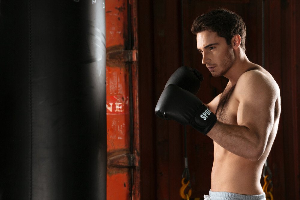 Photo of young strong boxer training in a gym. Looking aside. Standing near punchbag.