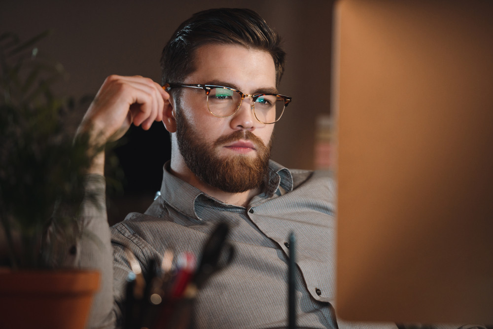 Photo of young web designer dressed in shirt and wearing eyeglasses working late at night and looking at computer. Holding pencil.