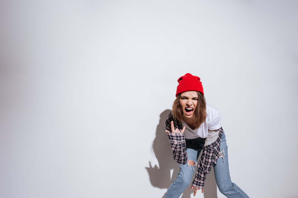 Photo of young woman dressed in shirt in a cage print standing isolated over white background make rock gesture
