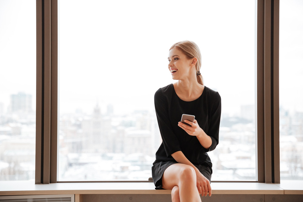 Photo of young woman worker sitting in office near window while looking aside and chatting by her phone.
