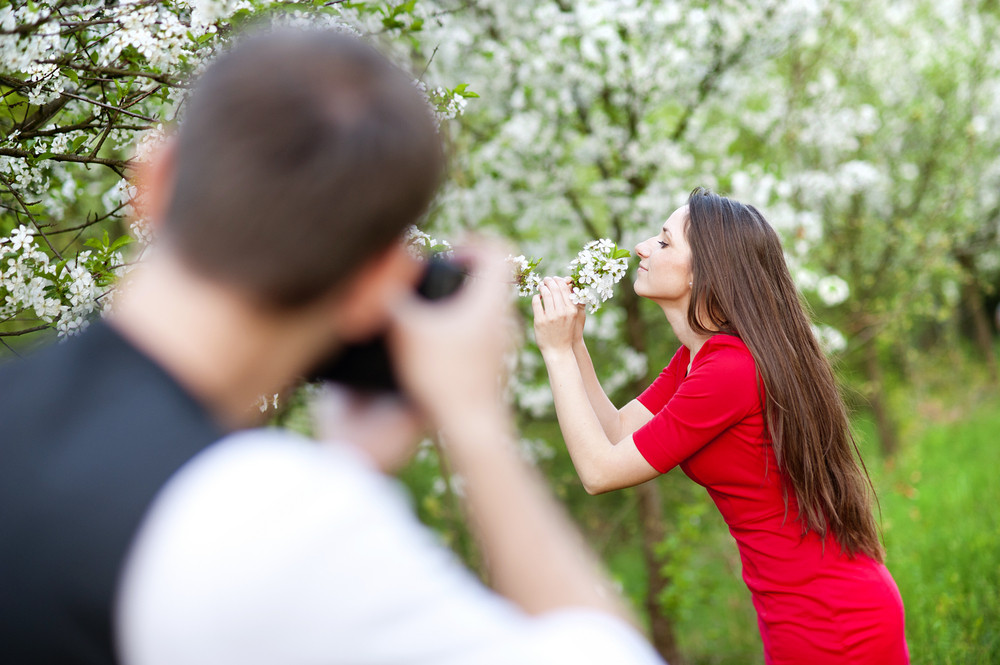 Photographer is taking photos of beautiful woman in red dress in nature