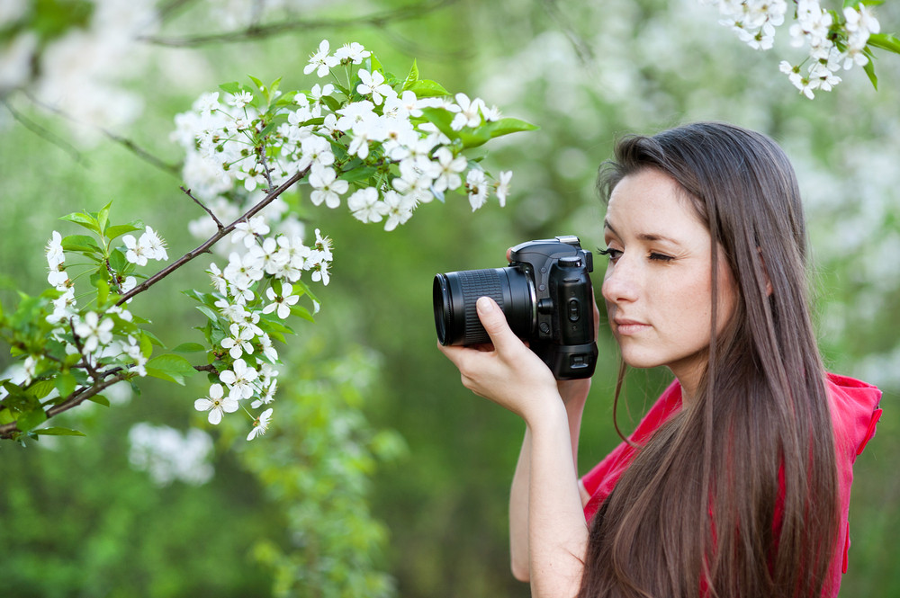 Photographer woman is taking photos in green park