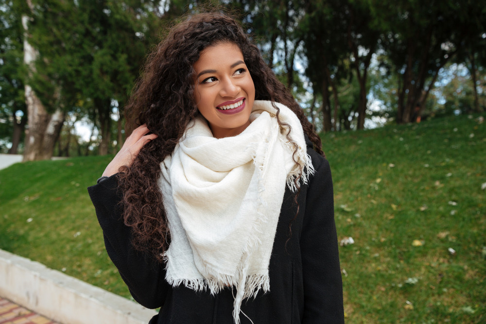 Photography of beautiful young african curly lady wearing big white scarf touching her hair and look aside with smile outdoors.