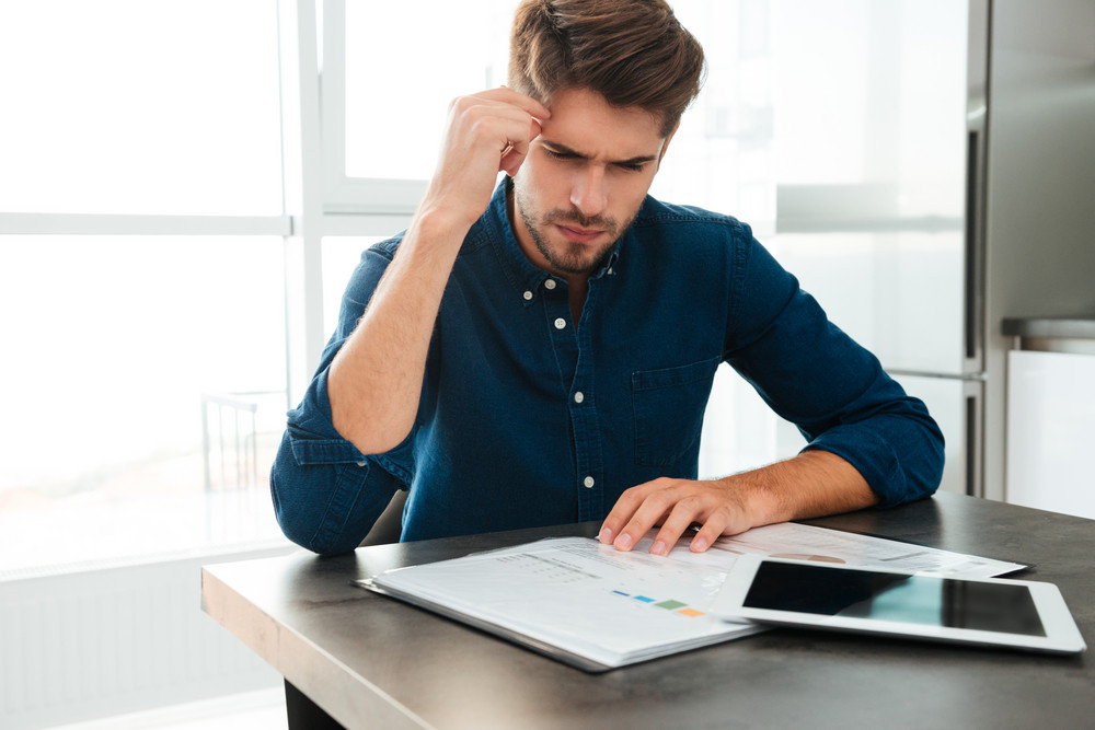 Photography of concentrated young man sitting at home and analyzing his finances. Looking at documents and touching his head.