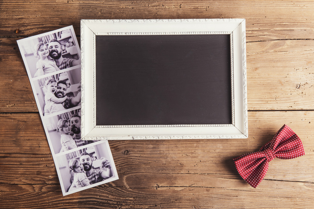 Picture frame, instant photos and a bow tie on wooden background.