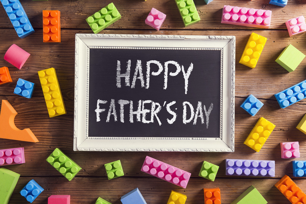 Picture frame with Happy fathers day sign laid on wooden background.