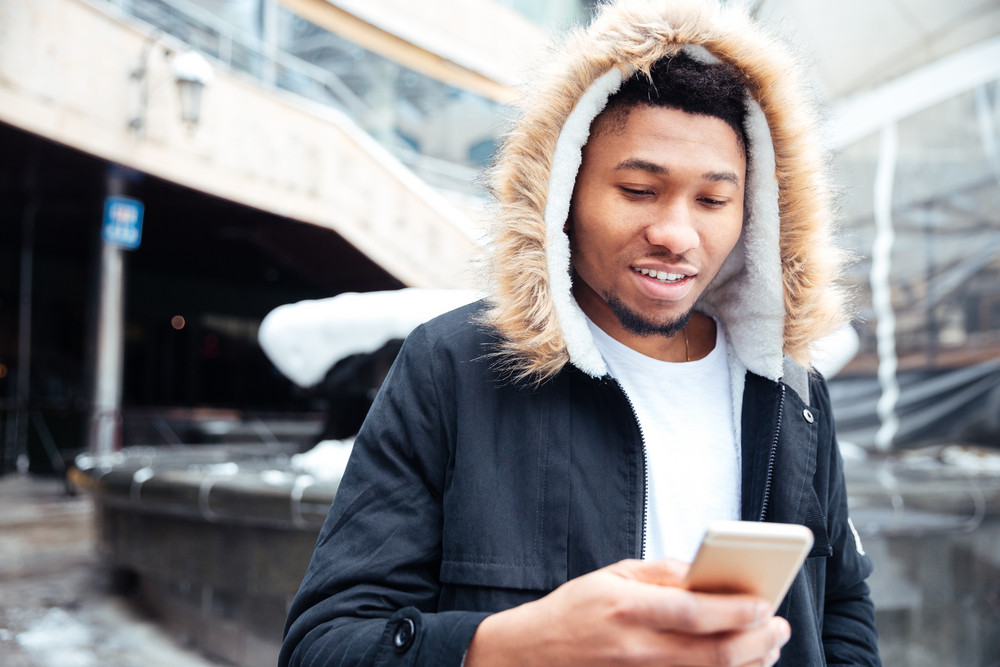 Picture of a handsome african young man walking on the street while using his phone. Looking at phone.